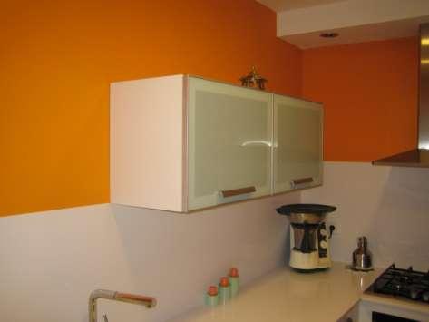 El encanto del naranja, una cocina en L y paralela